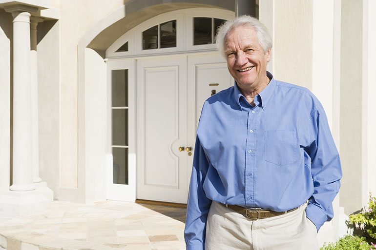 man standing outside front door of house